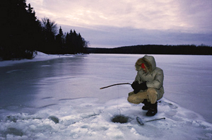 Ice fishing in the Canadian Rockies of Western Canada.